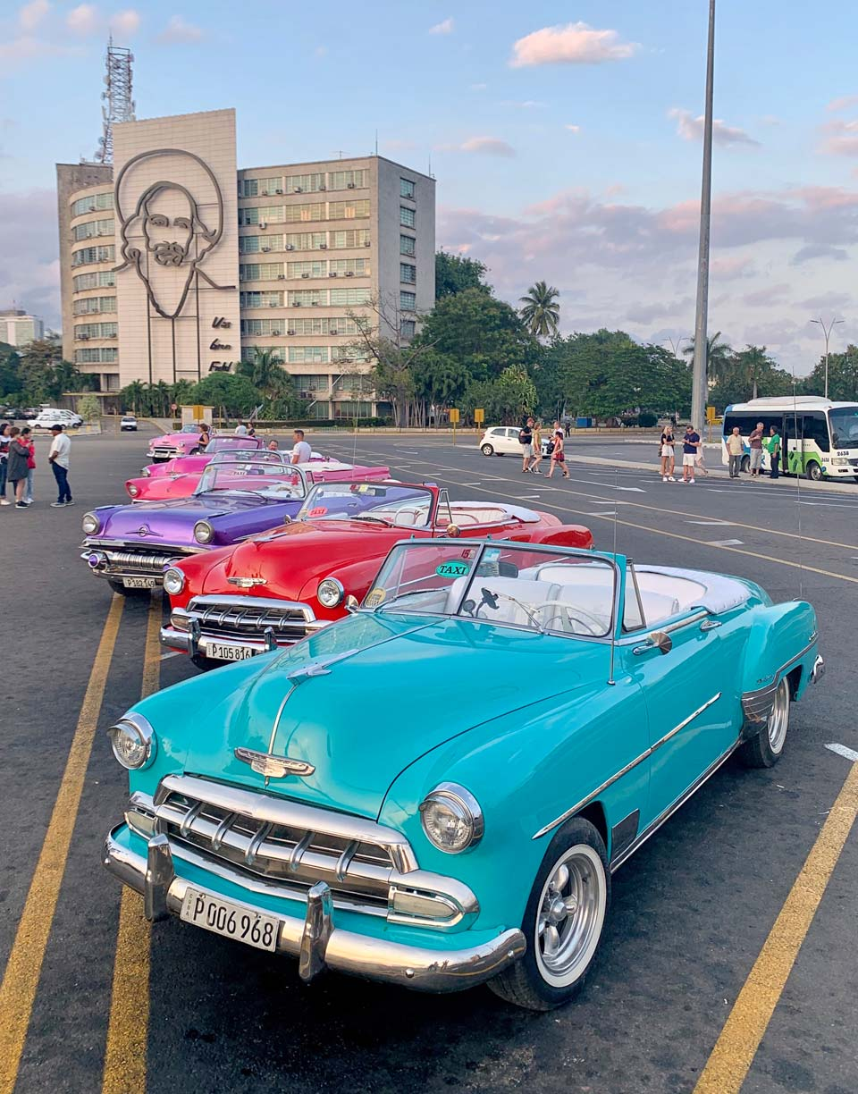 Vintage cars line up in front of a giant portrait of Camilo Cienfuegos, Commanding Officer of the Revolutionary Army.