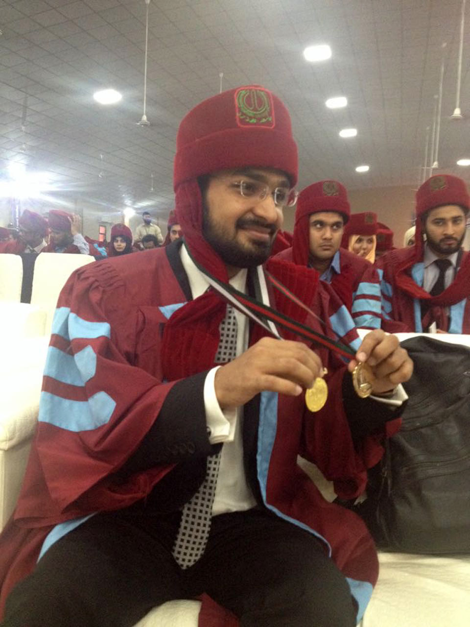 A fresh graduate is showing his Gold Medal to his friends