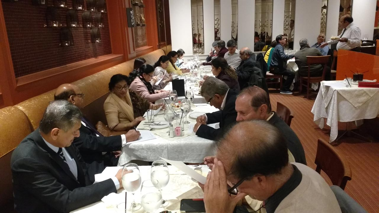 Aramcons concentrating on the Word jumble and Word Search games prepared by Tanaz (Khory) Jivraj. On the left side of the tables fr front to back: Anwar Baig, Yousef and Fareeda Syed, Farhat Begum, Sabiha Pasha, Nabila Naeem, and Ada Kwan. On the right side of the tables from front to back: Masroor Khan, Anwar Khan, Gul Sheikh, Fareeda Yasmin, Nishad Pasha, Shahid Naeem, Wilfred Carvalho, Wing Kwan. On the extreme right is Javaid Hamid (holding a plate) in conversation with Ahmed Munir and Mohamed Patel