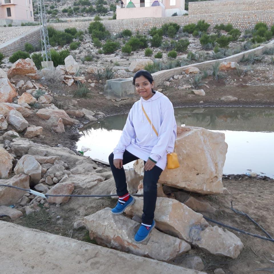 Zoya is enjoying on a rock beside a lake