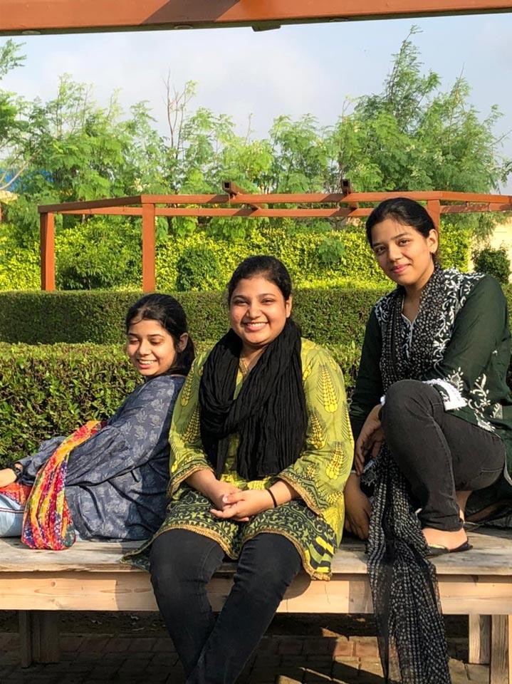 Zara, Fareena and Zoya sitting on a bench, sun kissed.