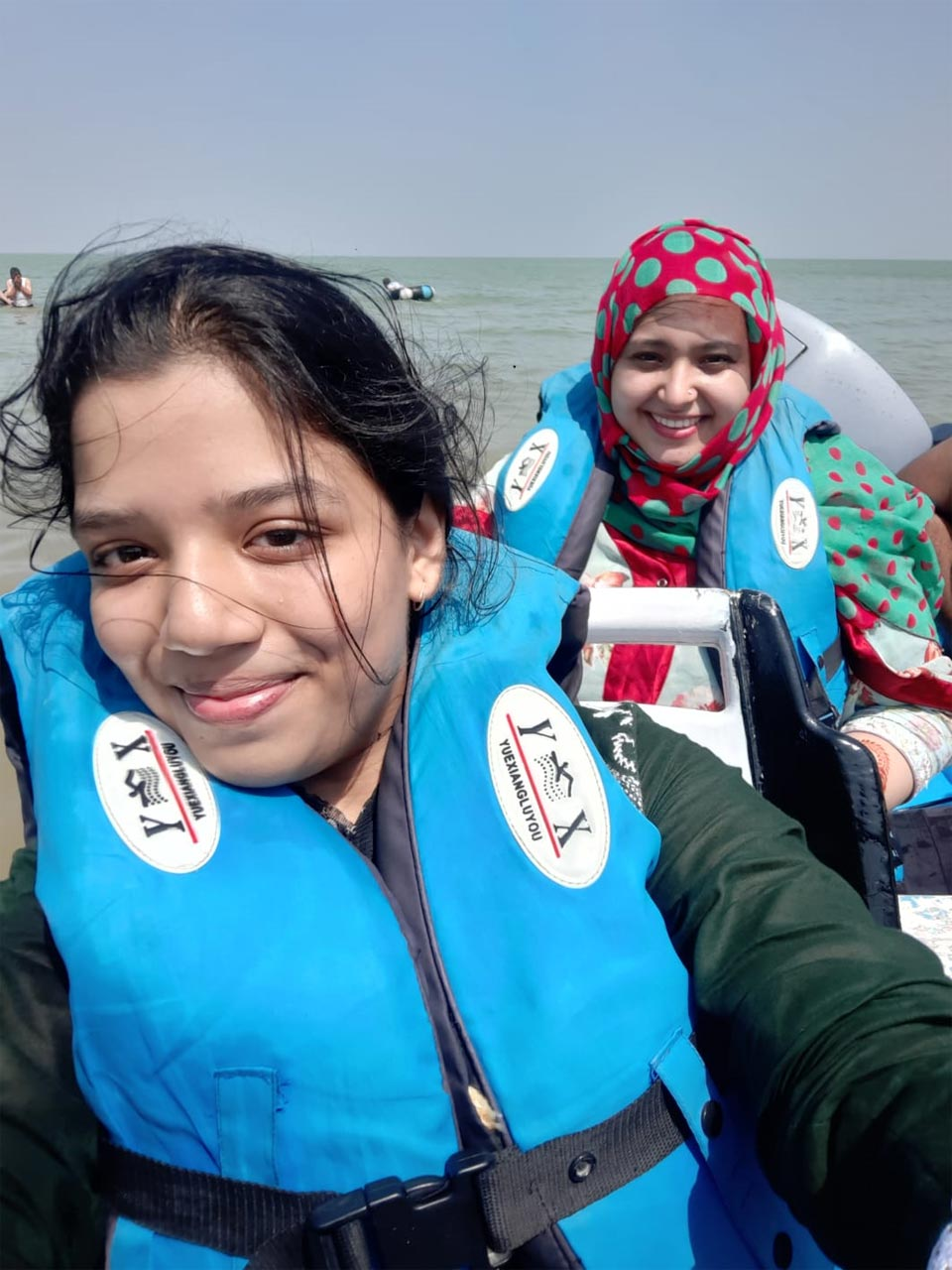 Zoya and Samia in lifejackets, ready for the boat journey.