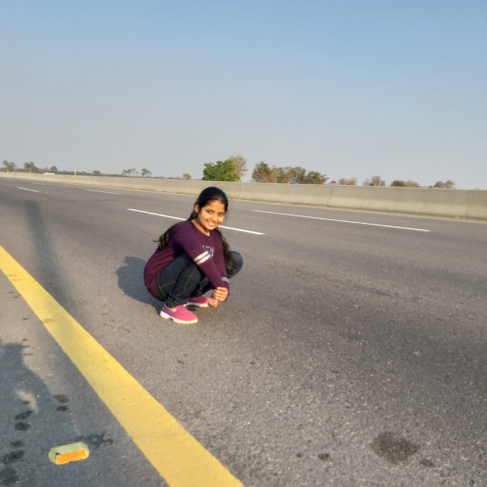 Zara Imran posing for the picture while sitting on the road of the Sukkur, Multan Motorway.