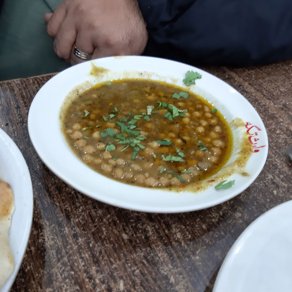 The family is enjoying the traditional Murgh Chana of Lahore.