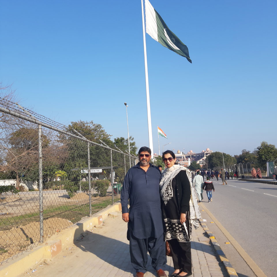 Imran Khan and Erum Imran are standing with Pakistan's National flag @ Wagah.
