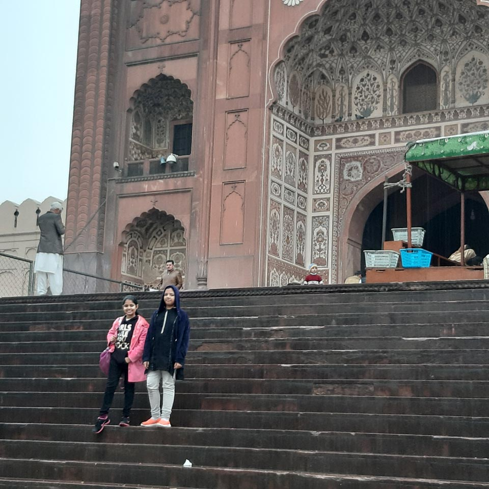 Zoya and Zara in front of the entrance stairs of the Badshahi Mosque of Lahore.