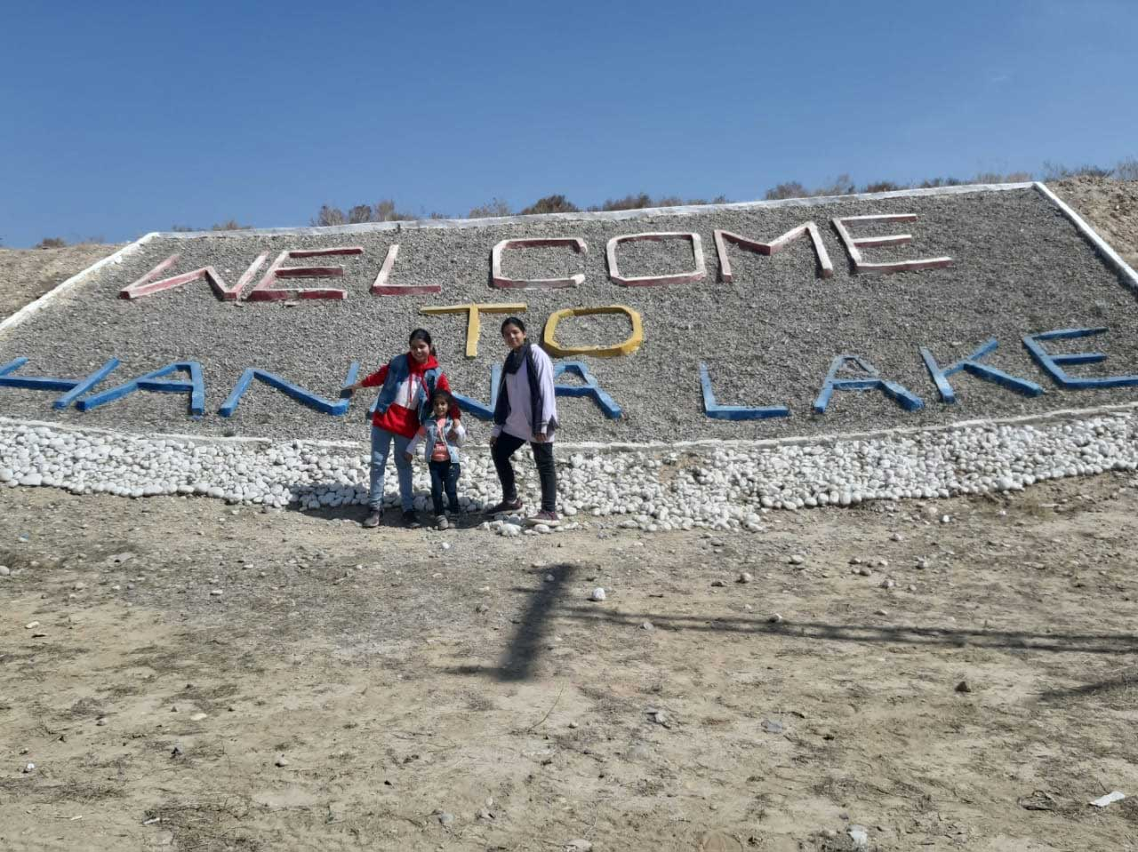 Zara, Ayesha and Zoya in front of the welcome sign of Hanna Lake