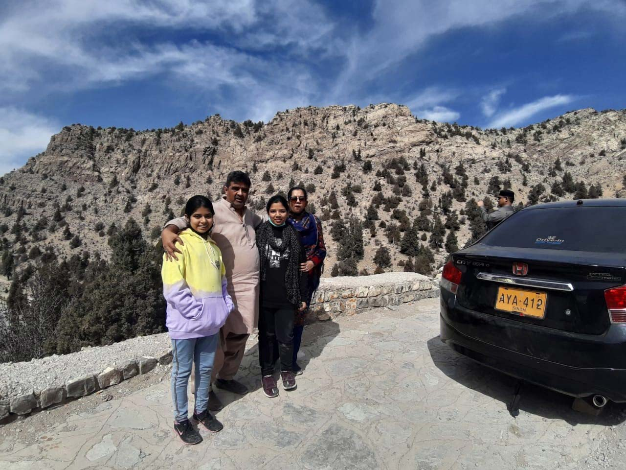 Imran and Family in front of a mountain in Quetta where the clouds are about to start raining