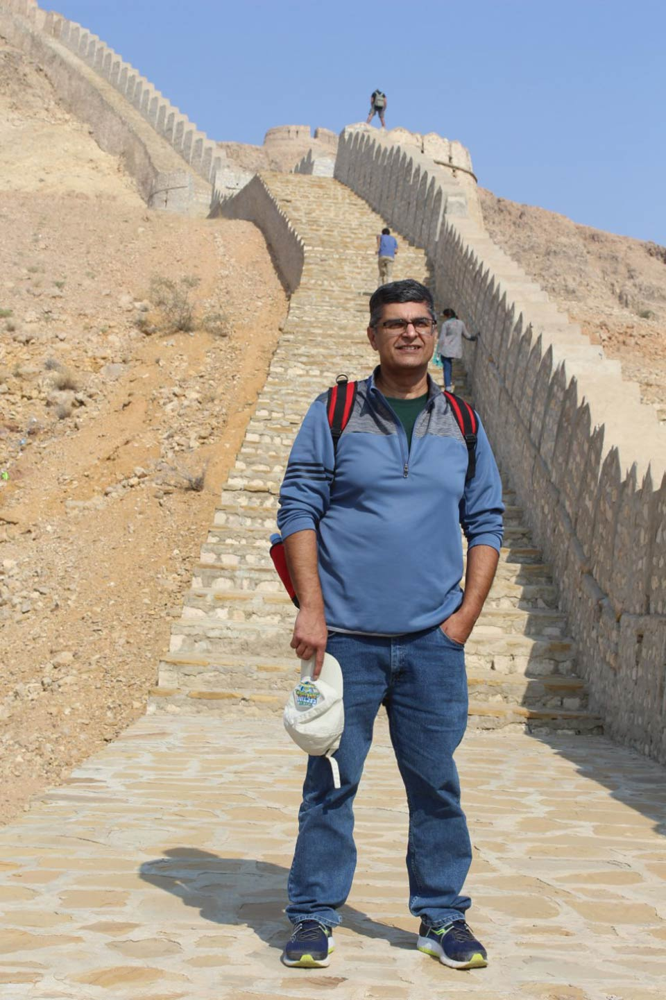 Mr. Faisal Saeed from California USA right in front of the stairs along with the great wall of Rani Kot