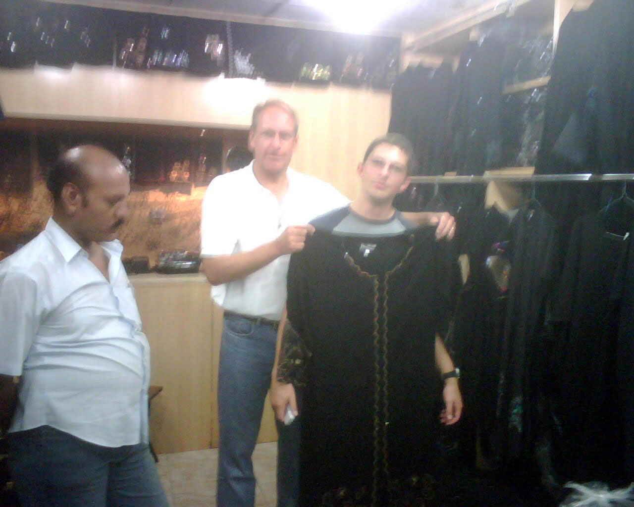 """In the children's clothing shop, Michael reluctantly agrees to """"model"""" an abaya. © Mark Lowey"""