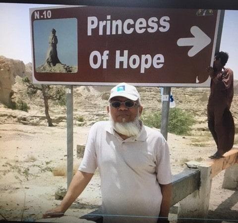"Engr. Iqbal Khan under the sign board for ""Princess of Hope"" on the Makran Coastal Highway."