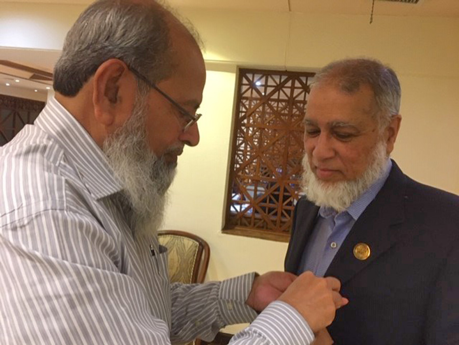 Engr. Muhammad Hamid is fixing the NED College Pin on Khalid coat