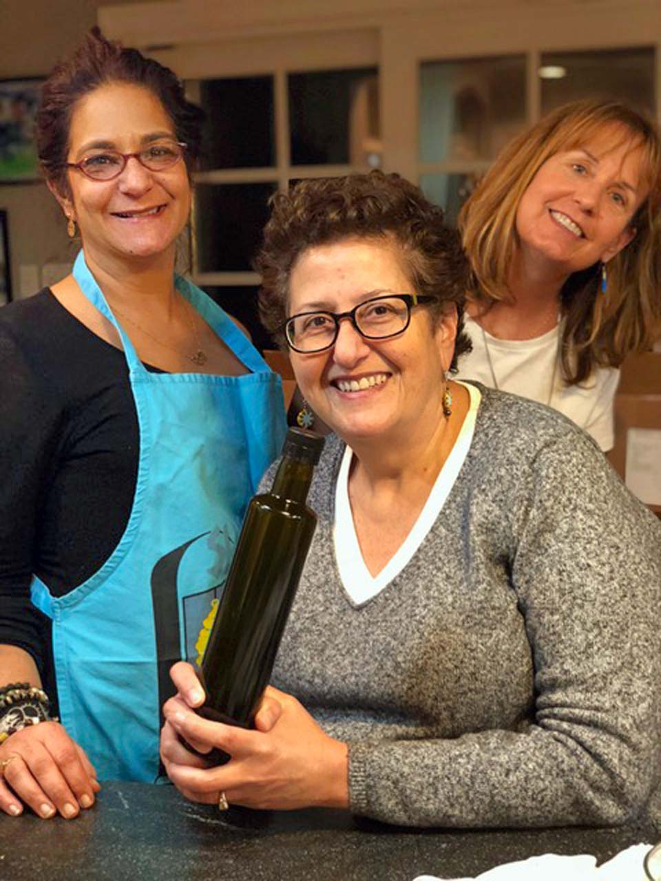 Julie Sawaya, Raidah Ziadeh Hudson and Bridget Mulligan with a filled bottle of olive oil
