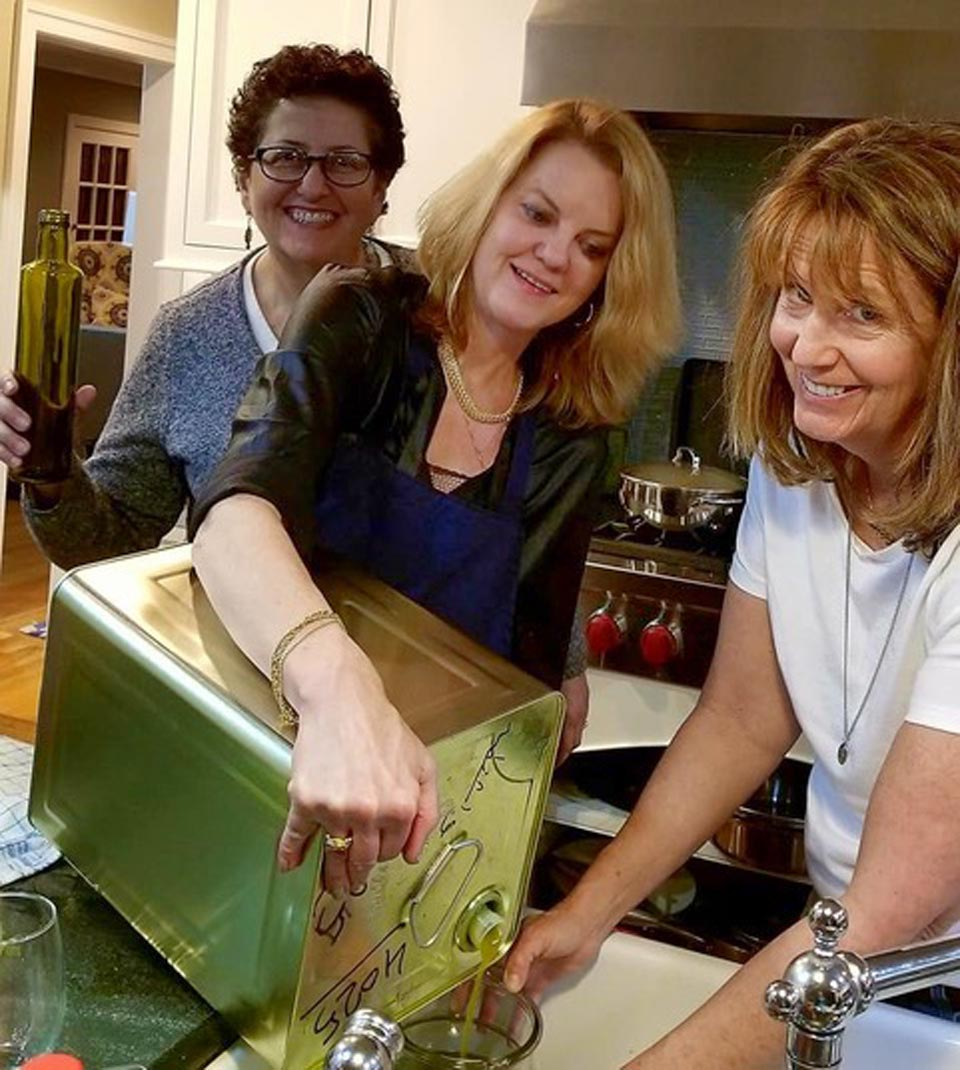 Raidah Ziadeh Hudson, Lisa Jacobs (holding olive oil tanaka) and Bridget Mulligan (directing olive oil into pitcher).