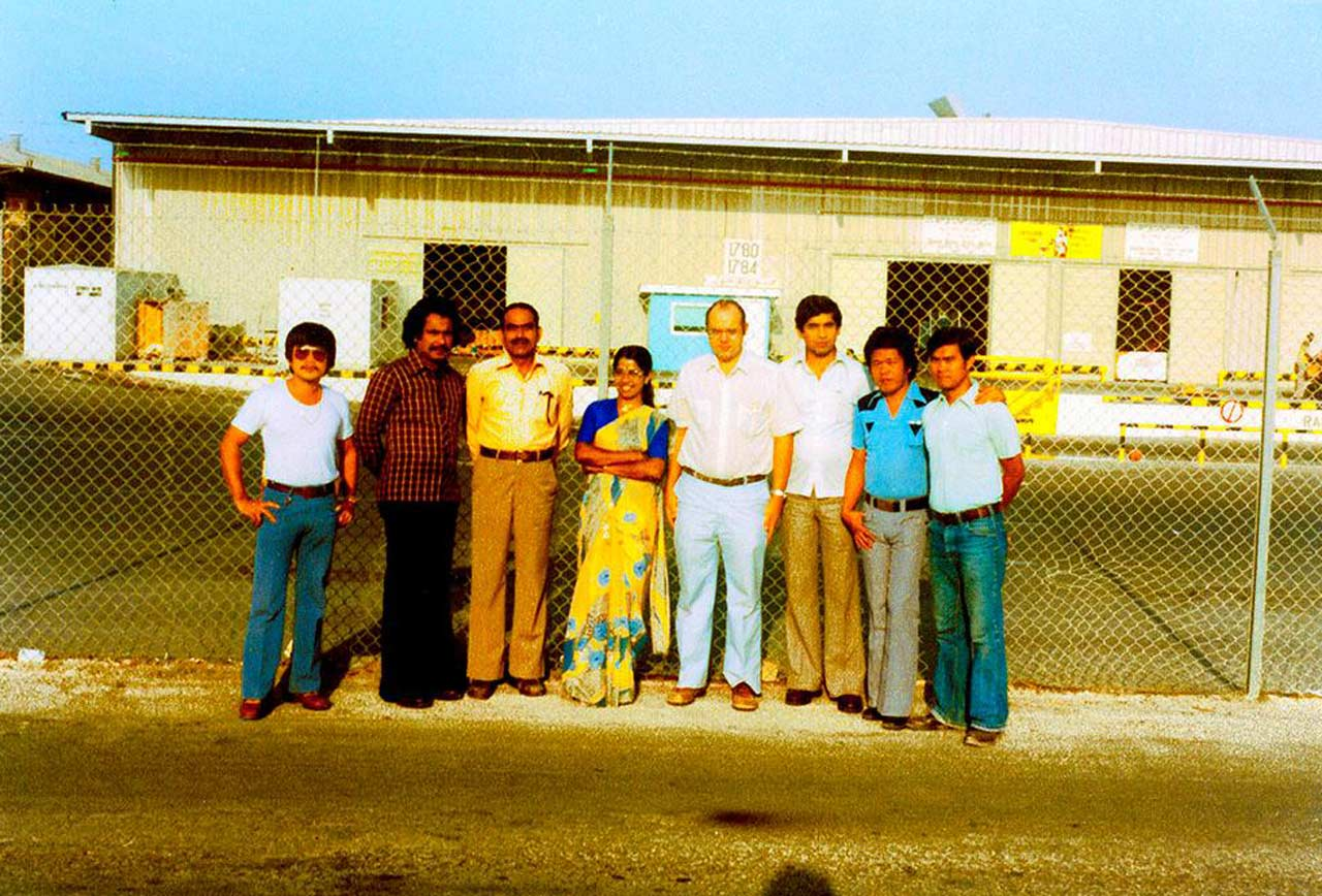 "Material Supply ""Uncleard Charges"" group outside Material Supply Warehouse, Dhahran around 1981"