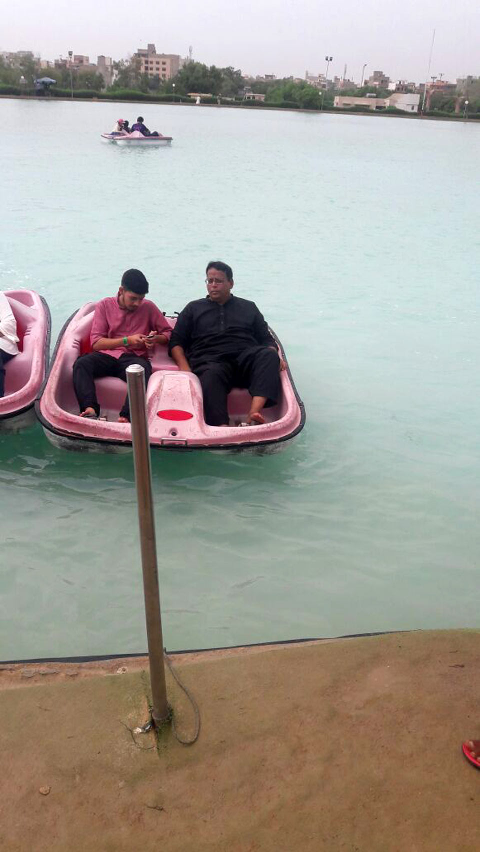 Dr. Ata Ur Rehman and Obaid Ur Rehman are enjoying the paddling boat