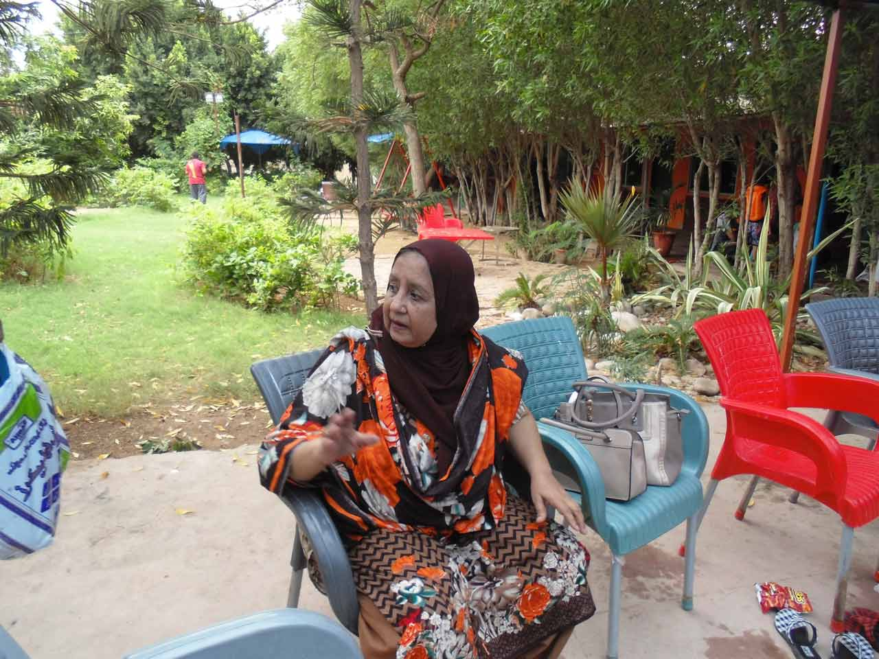 Mrs. Shafiq Ahmed Khan enjoying the weather outside the swimming pool