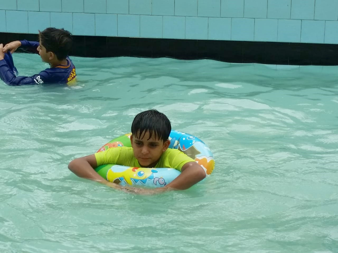 The kid is enjoying inside the swimming pool