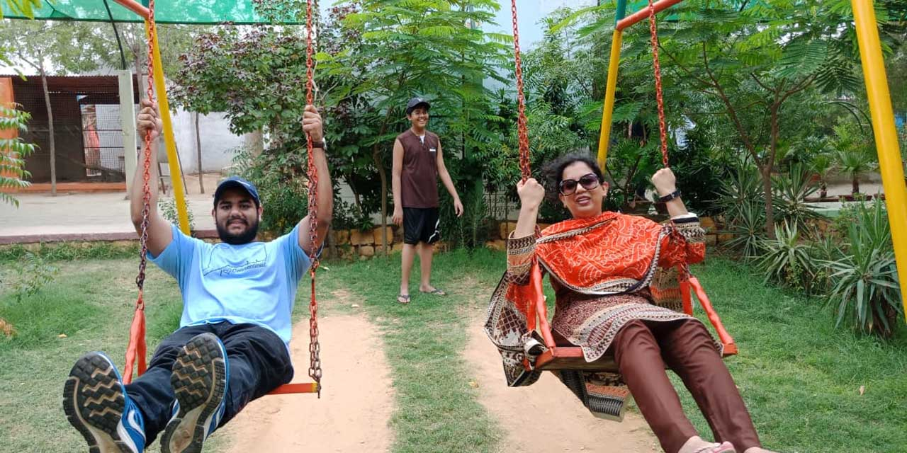 Engr. Taha A. Khan and Erum Imran are enjoying on the swings while Habib is assisting them