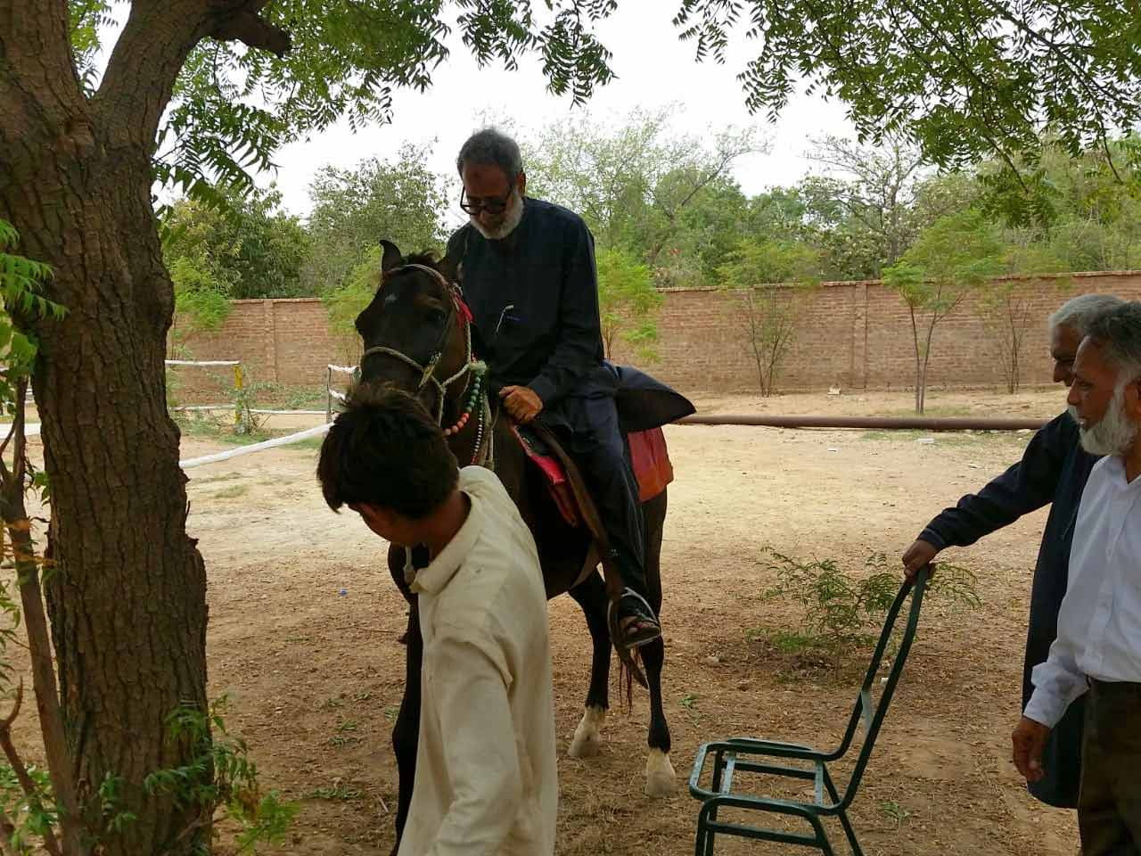 Syed Shahid Ali is enjoying the horse ride while M. Ibrahim and Shahid Qadri are watching