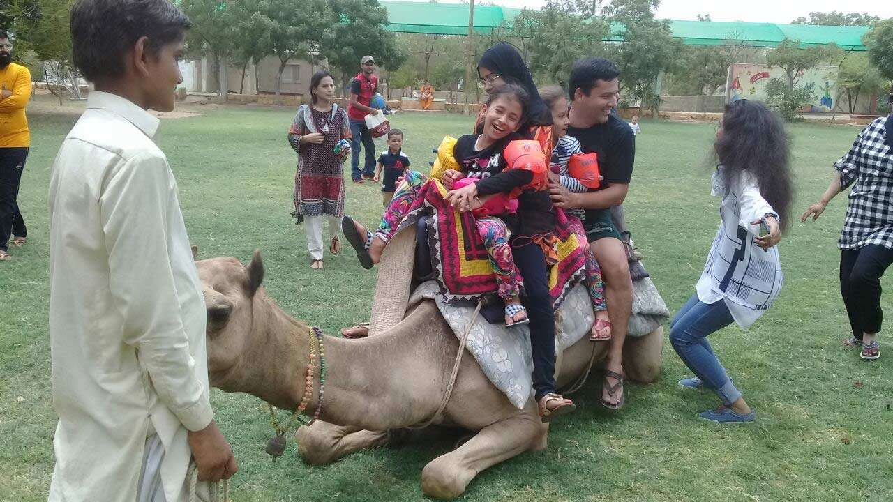 Imran along with his daughters enjoying the camel ride at the farm house