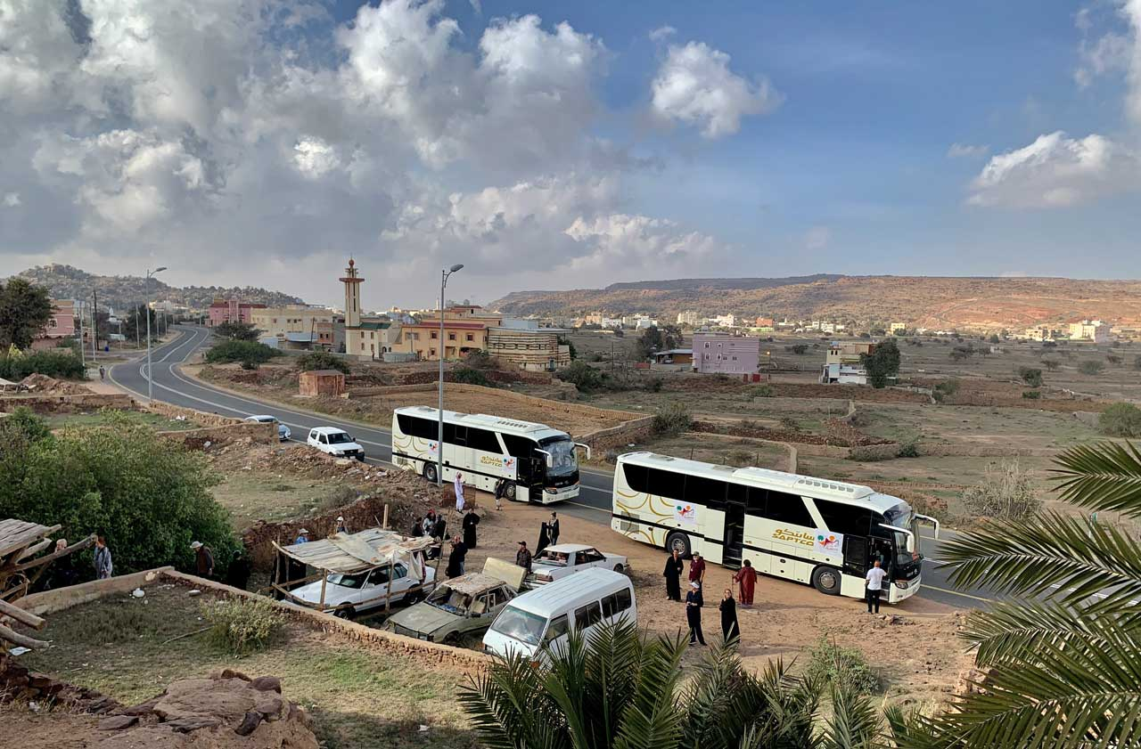 Our two tourist coaches arrive at Al Yanfa village. © Mark Lowey.