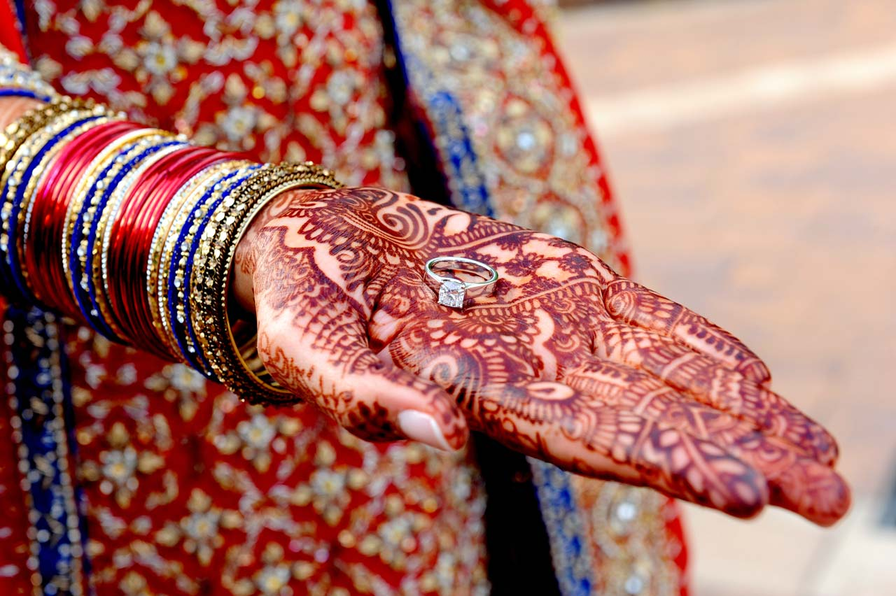Aneela (bride) is showing off her ring on henna decorated hand.