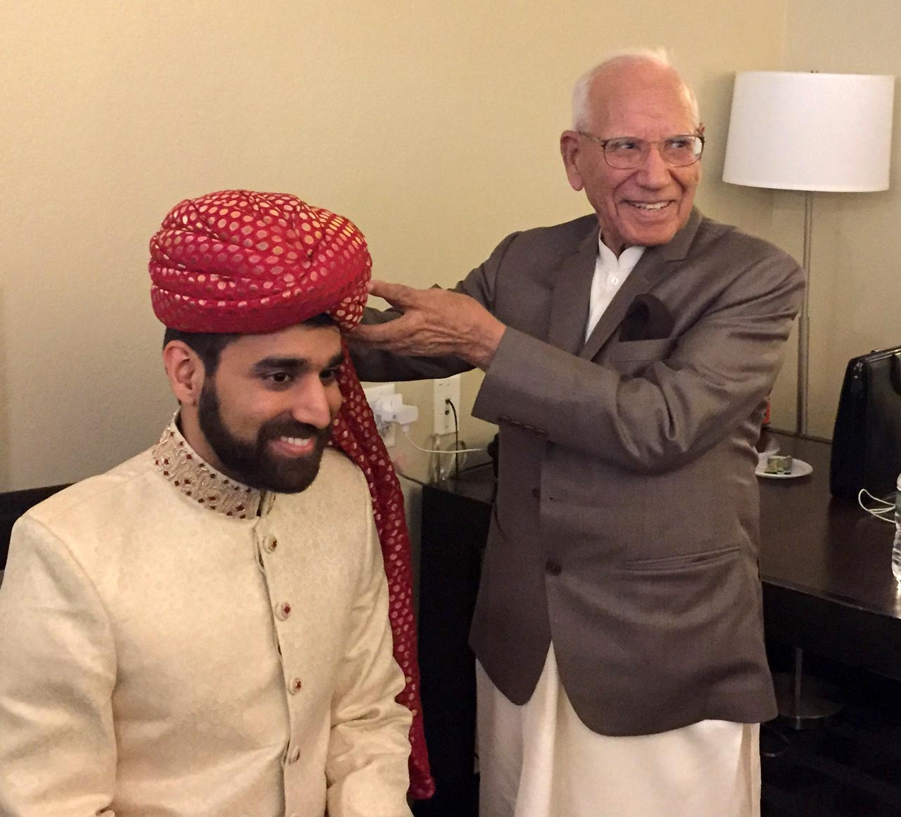 Shaikh Amin as the family elder, putting on a traditional wedding turban on his grandson's head.