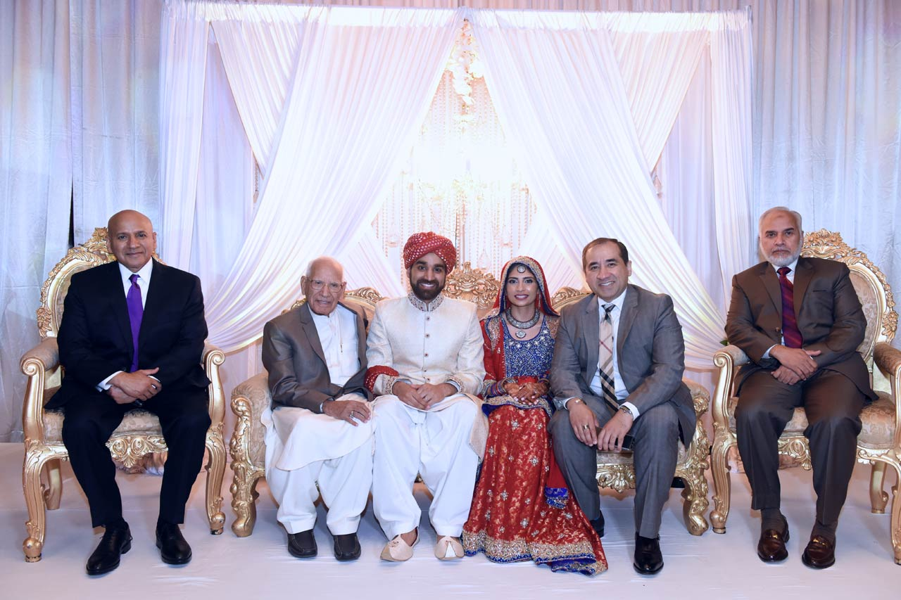 Shaikh Amin along with his three sons (Tariq, Shahid, and Zahid) posing with the newlyweds.