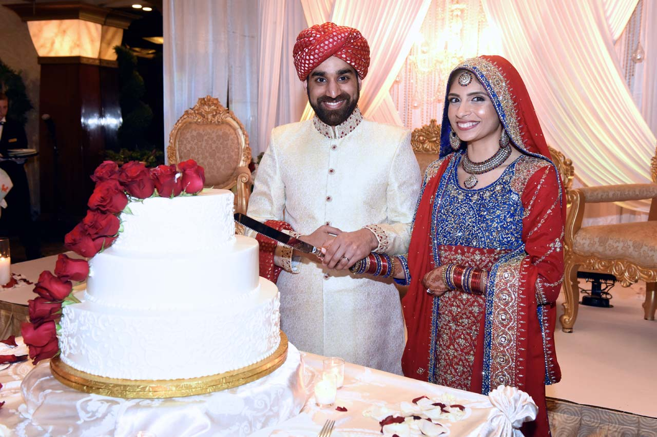 Hammad and Aneela posing next to their wedding cake.