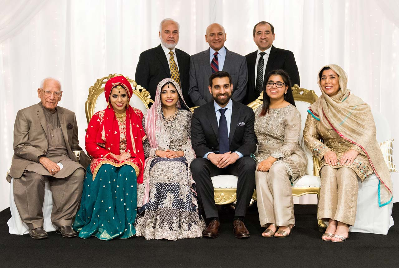 Shaikh Amin, with his three sons Tariq, Shahid, and Zahid in the back, posing with Shahid's family and the newlyweds.