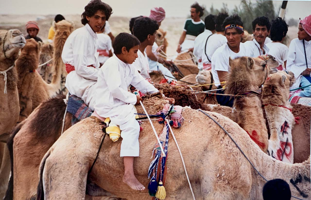 Camel jockeys, ranging in age from roughly 8 to 20, prepare to race. © Mark Lowey.