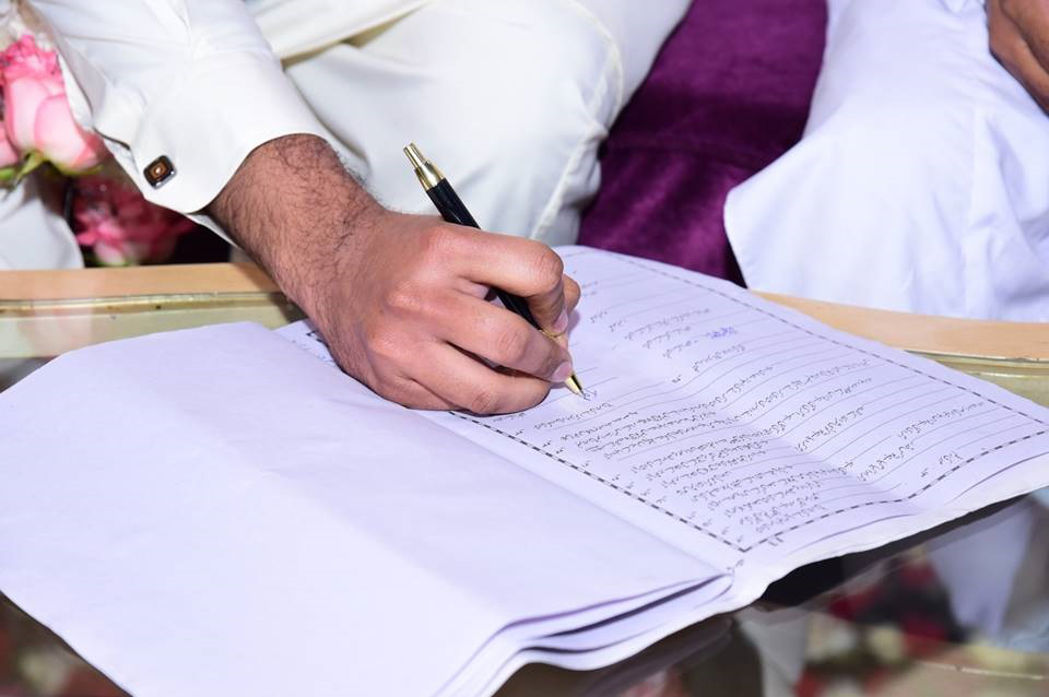 The Bride Groom is signing the Nikah document