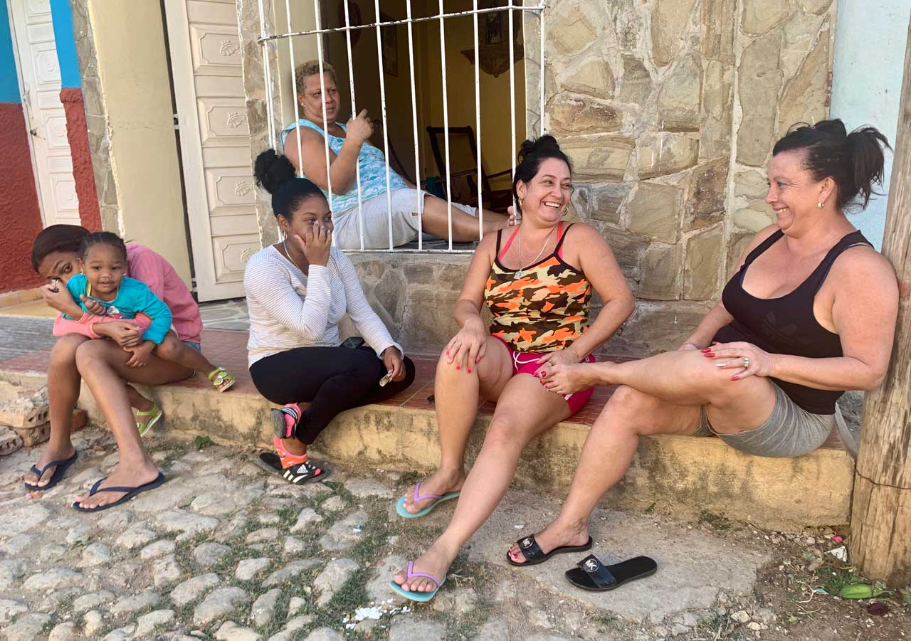 Women relax in front of their home and chat with us.