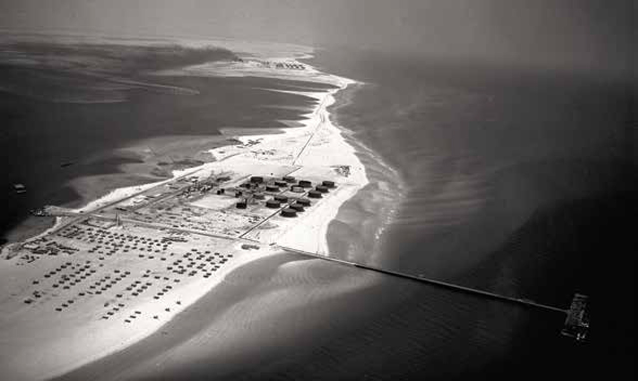 Shown in the mid-1940s, the Ras Tanura Refinery complex spanned the entire width of a narrow sand spit. Rows of tanks stored oil for export tankers calling at the terminal.