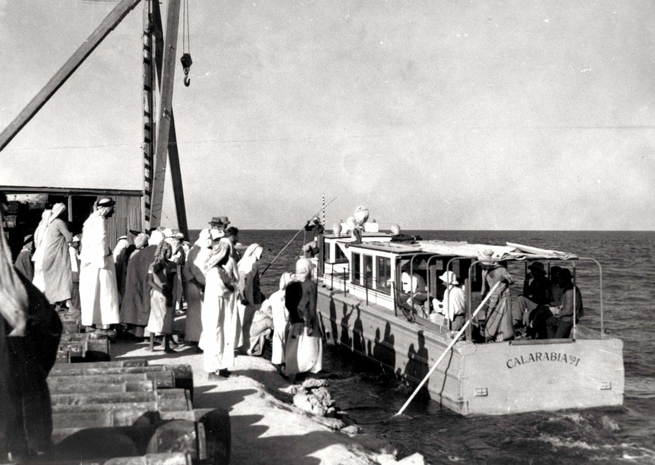 Residents board a boat for Bahrain in the late 1930s, long before the causeway provided an automobile route to the island. Floyd Ohliger, a prominent figure in Aramco history, supervised the construction of the al-Khobar pier, the very first of its kind. The boat Calarabia departed regularly to Bahrain from the pier. (Photo: Max Steinke)