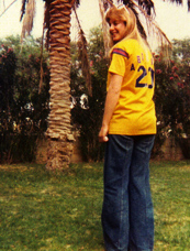 Vicky in her All Star Softball Team uniform in the apartment front yard
