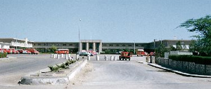 A view of the Aramco Administration Building in Dhahran, with its fleet of bright red cars and buses, mid-1950s.