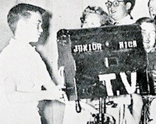 "Dhahran junior high school student Craig Miller plays a TV cameraman during the annual ""minstrel show."""