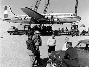 Three Aramco cranes lift the giant KLM DC-4 onto a truck bed on the morning of January 2, 1953.