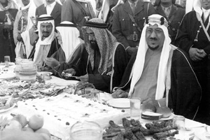 King Saud, right, at an elegant seated dinner during one of his visits to Dhahran in the 1950s.