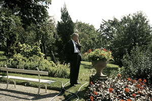 Ken Webster enjoys a cigarette while admiring the gardens on the grounds of Brillantmont in Lausanne.
